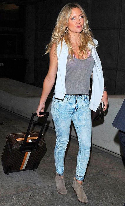Chaleco sport + camiseta + jeans desgastados: Aquí se combina prendas básicas con unos cómodos botines para un viaje en avión.