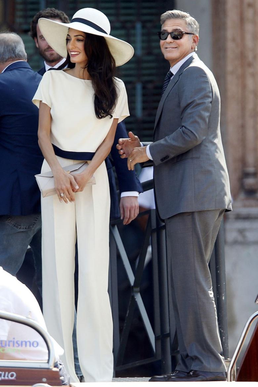 Augurando una primavera de novias con pantalones, Amal Alamuddin eligió unos para su ceremonia civil con George Clooney. Un impresionante conjunto compuesto por top y pantalón blanco, y pamela. Ambos estaban adornados con un ribete azul; un detalle que confería al look cierto espíritu navy.